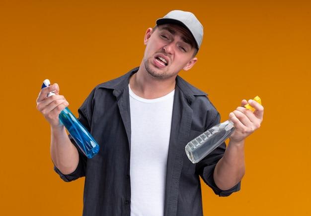 Unzufriedener, kippender junger, gutaussehender putzmann mit t-shirt und mütze mit sprühflaschen isoliert auf oranger wand