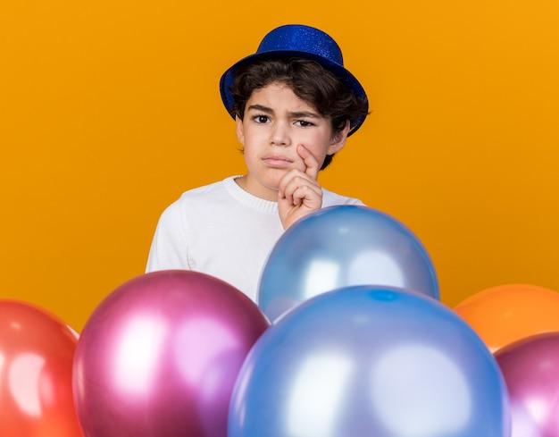Unzufriedener kleiner junge mit blauem partyhut, der hinter luftballons steht, packte das kinn