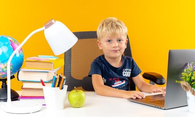 Unzufriedener kleiner schuljunge, der mit schulwerkzeugen am tisch sitzt, benutzte laptop