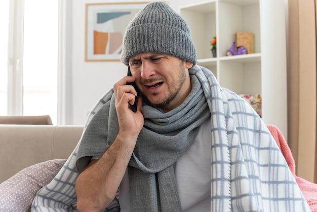 Unzufriedener kranker mann mit schal um den hals, der eine wintermütze trägt, die in plaid gehüllt ist und am telefon auf der couch im wohnzimmer sitzt