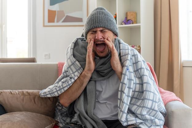 Unzufriedener kranker mann mit schal um den hals, der eine wintermütze trägt, die in plaid gehüllt ist und die hände nah am mund hält, indem sie jemanden anruft, der auf der couch im wohnzimmer sitzt