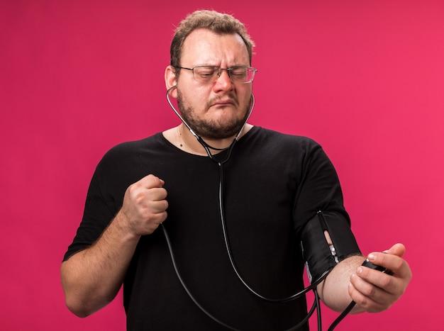Unzufriedener kranker mann mittleren alters, der seinen eigenen druck mit einem auf rosafarbener wand isolierten blutdruckmessgerät misst