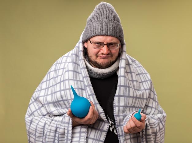 Unzufriedener kranker mann mittleren alters mit wintermütze und schal, der in karierte einläufe gehüllt ist