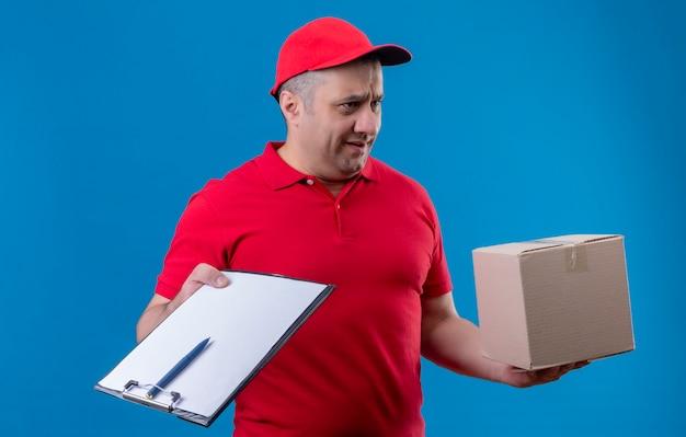 Unzufriedener lieferbote, der rote uniform und kappe hält, die kastenpaket und zwischenablage hält und beiseite schaut mit stirnrunzelndem gesicht über blauem raum steht
