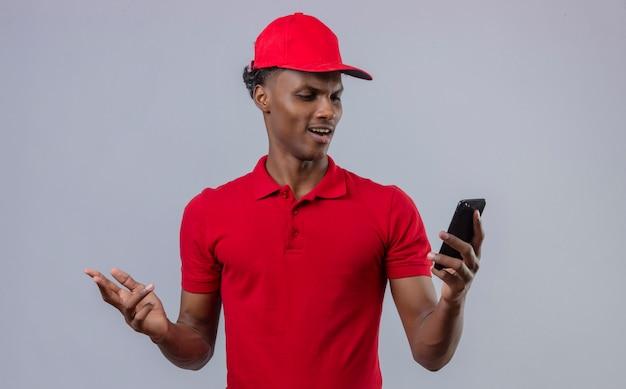 Unzufriedener lieferbote des jungen afroamerikaners, der rotes poloshirt und kappe trägt, die smartphone in der hand betrachten, die abneigung über isoliertem weiß zeigt