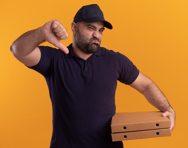 Unzufriedener liefermann mittleren alters in uniform und mütze mit pizzakartons mit daumen nach unten isoliert auf gelber wand