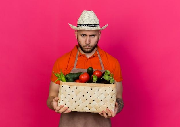 Unzufriedener männlicher gärtner, der gartenhut trägt, hält gemüsekorb