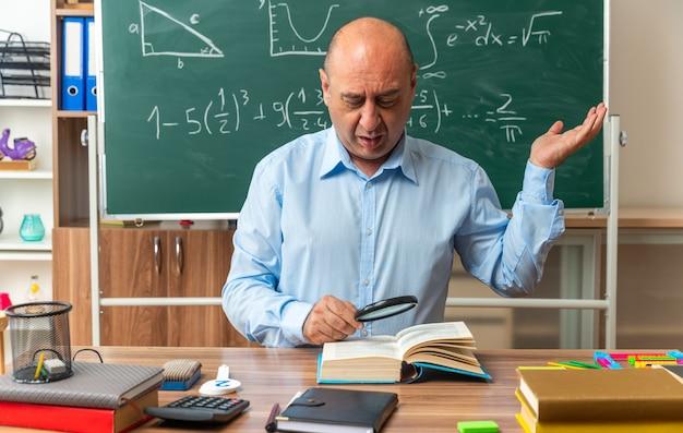 Unzufriedener männlicher lehrer mittleren alters sitzt am tisch mit schulmaterial und liest ein buch mit lupe, die die hand im klassenzimmer ausbreitet