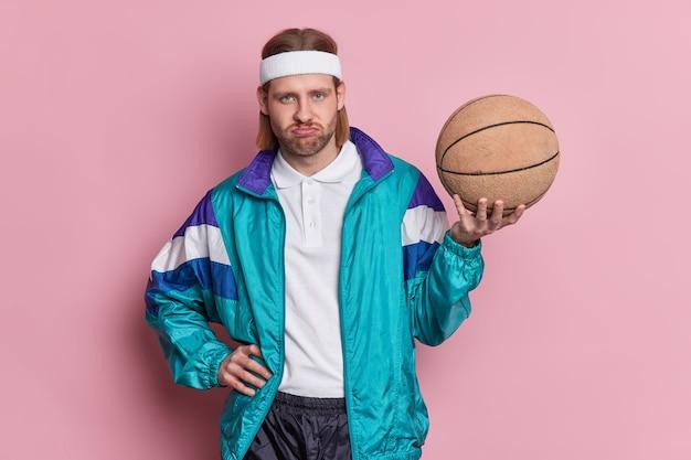 Unzufriedener mann basketballspieler hält ball schaut unglücklich in die kamera