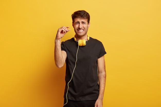 Unzufriedener mann beißt die zähne zusammen, zeigt eine winzige geste, sagt ein bisschen mehr, trägt ein lässiges schwarzes t-shirt und hat kopfhörer zum anhören der wiedergabeliste