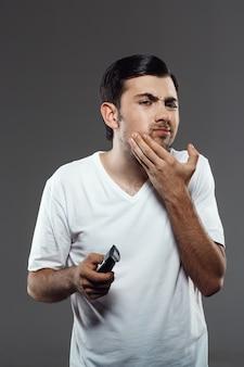Unzufriedener mann, der sich mit elektrorasierer rasiert