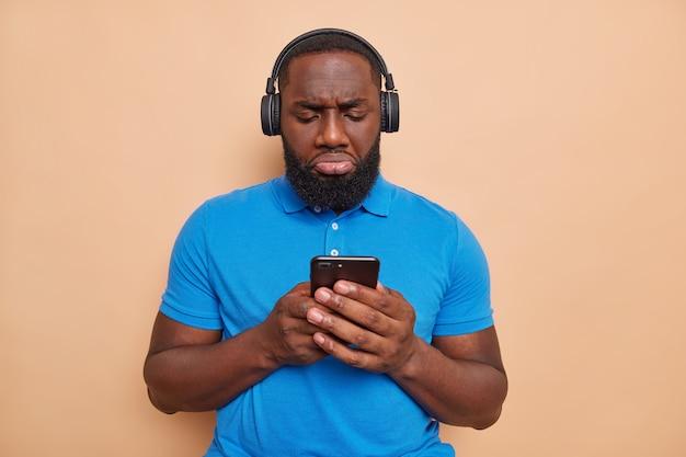 Unzufriedener mann mit dickem bart schreibt textnachrichten über smartphone, die unglücklich sind, schlechte kommentare unter post zu lesen, hört musik über kopfhörer trägt blaues t-shirt posiert braune innenwand