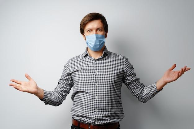 Unzufriedener mann mit medizinischer maske, die mit erhobenen händen steht