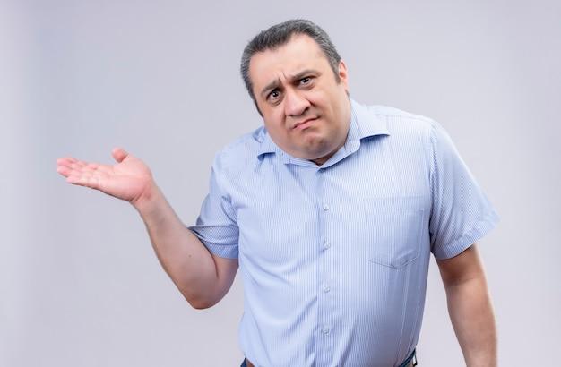 Unzufriedener mann mittleren alters, der blaues hemd mit vertikalen streifen trägt und seine hand im stehen ausbreitet