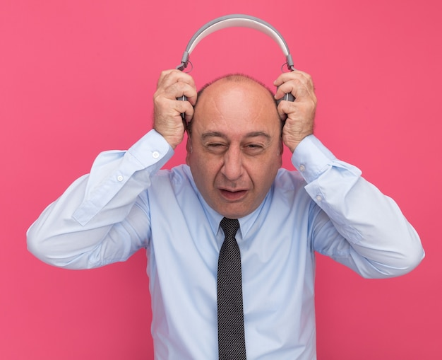 Unzufriedener mann mittleren alters, der weißes t-shirt mit krawatte trägt, die kopfhörer auf kopf lokalisiert auf rosa wand setzt