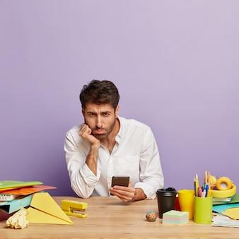 Unzufriedener mitarbeiter sitzt am schreibtisch