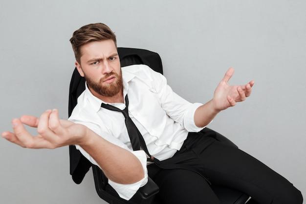 Unzufriedener müder geschäftsmann, der auf einem stuhl sitzt