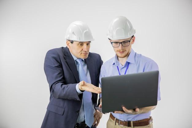 Unzufriedener projektleiter und chefingenieur in schutzhelmen diskutieren neues projekt