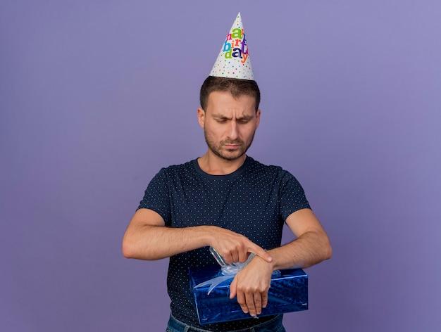 Unzufriedener schöner kaukasischer mann, der geburtstagskappe hält, hält und betrachtet geschenkbox lokalisiert auf lila hintergrund mit kopienraum