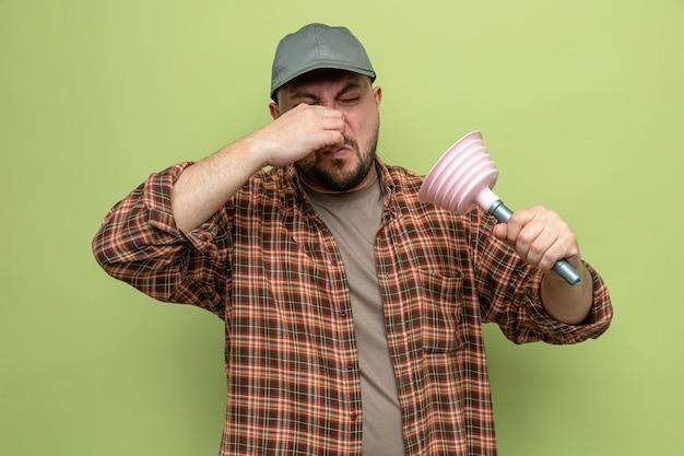 Unzufriedener slawischer putzmann, der einen gummikolben hält und seine nase schließt