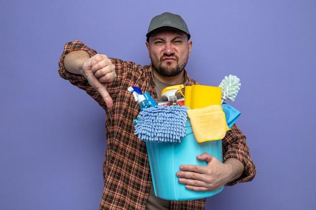 Unzufriedener slawischer putzmann, der reinigungsgeräte hält und runterdrückt