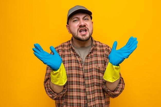 Unzufriedener slawischer putzmann mit gummihandschuhen, die die hände offen halten