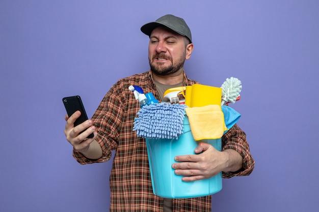 Unzufriedener slawischer reinigungsmann, der reinigungsgeräte hält und auf das telefon schaut