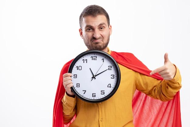 Unzufriedener superheld mann mit rotem umhang hält und zeigt auf uhr isoliert auf weißer wand