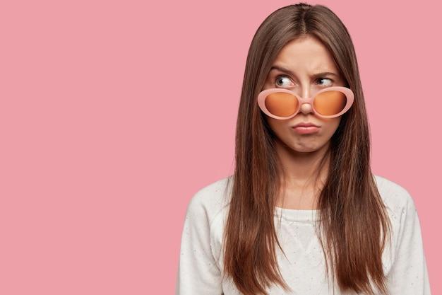 Unzufriedener teenager sieht mit düsterem negativen gesichtsausdruck aus, schmollt lippen