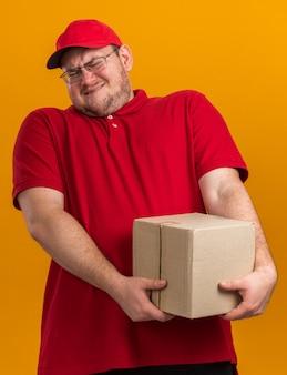 Unzufriedener übergewichtiger junger lieferbote in optischer brille mit karton isoliert auf oranger wand mit kopierraum