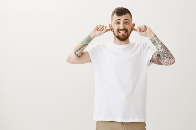 Unzufriedener und belästigter hipster-typ schloss die ohren vor lauten nervigen geräuschen