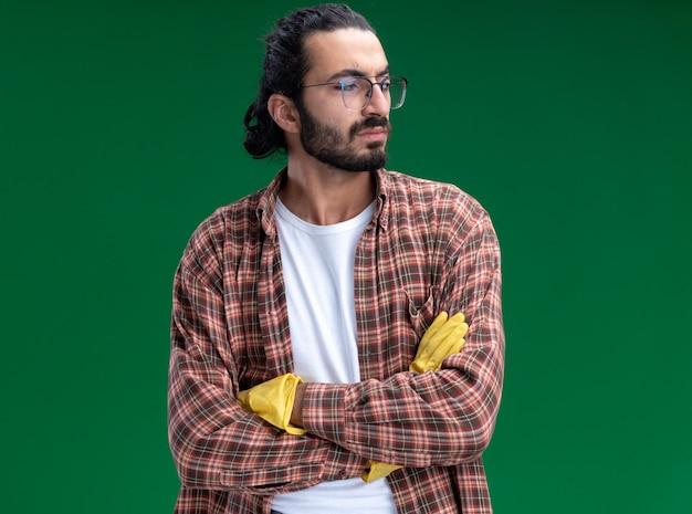 Unzufriedenes betrachten des jungen gutaussehenden putzmanns der seite, der t-shirt und handschuhe kreuzt, die hände lokalisiert auf grüner wand kreuzen