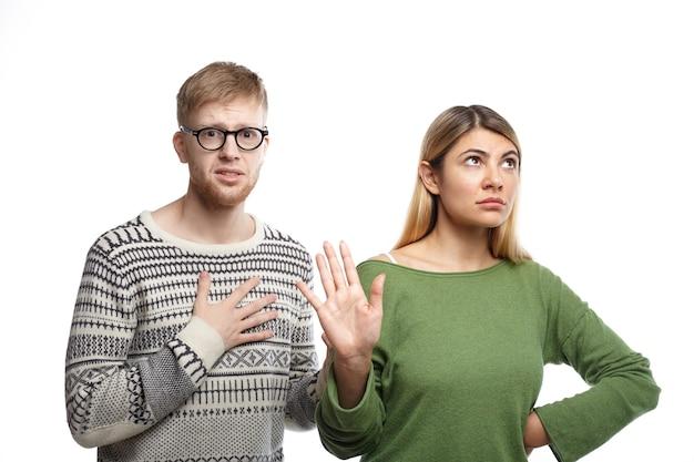 Unzufriedenes blondes mädchen zeigt stoppschild mit ihrer handfläche, was bedeutet, dass es vorbei ist, während ihr unglücklicher elender freund mit unglücklichem blick die hand auf seiner brust hält, als zeichen eines gebrochenen gehörs
