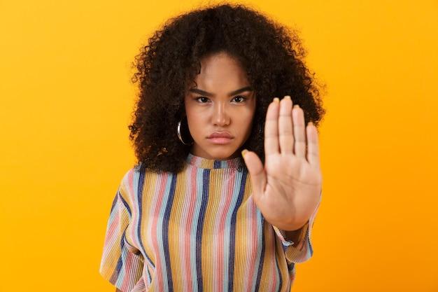Unzufriedenes junges afrikanisches süßes mädchen, das isoliert über gelbem raum aufwirft, machen stoppgeste.