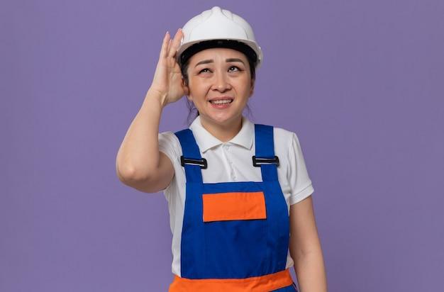 Unzufriedenes junges asiatisches baumeistermädchen, das hand auf ihren weißen schutzhelm legt und aufschaut