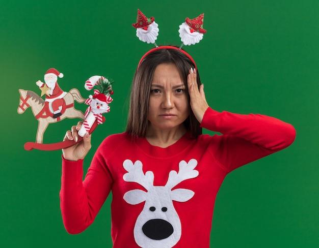 Unzufriedenes junges asiatisches mädchen, das weihnachtshaarbügel mit pullover hält, der weihnachtsspielzeug mit süßigkeiten setzt hand auf kopf lokalisiert auf grünem hintergrund hält