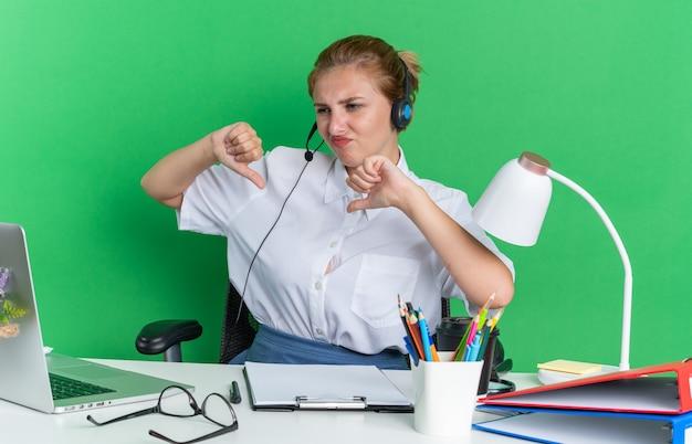 Unzufriedenes junges blondes callcenter-mädchen mit headset am schreibtisch sitzend mit arbeitswerkzeugen, die auf den laptop schauen und daumen nach unten zeigen