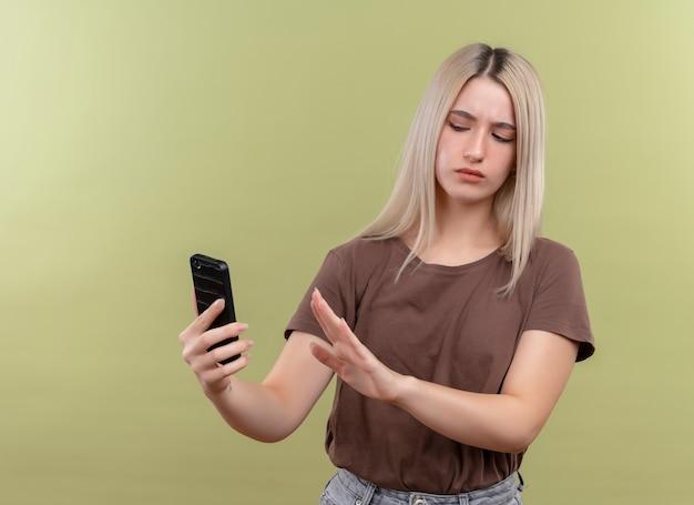 Unzufriedenes junges blondes mädchen, das handy hält, das es betrachtet und nein auf isolierte grüne wand mit kopienraum gestikuliert