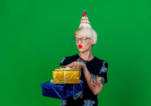 Unzufriedenes junges blondes partei-mädchen, das brille und geburtstagskappe hält, die geschenkboxen mit geschlossenen augen lokalisiert auf grünem hintergrund mit kopienraum hält
