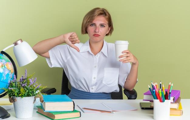 Unzufriedenes junges blondes studentenmädchen, das am schreibtisch mit schulwerkzeugen sitzt und plastikkaffeetasse hält, die daumen nach unten zeigt