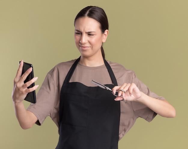 Unzufriedenes junges brünettes friseurmädchen in uniform hält eine schere zum ausdünnen des haares und schaut auf das telefon isoliert auf olivgrüner wand mit kopierraum