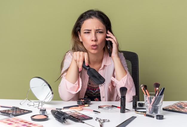 Unzufriedenes junges brünettes mädchen, das am tisch mit make-up-tools sitzt und am telefon spricht und einen kamm hält