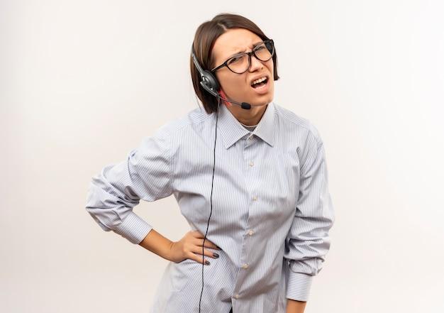 Unzufriedenes junges callcenter-mädchen, das eine brille und ein headset trägt, die hand auf taille lokalisiert auf weißem hintergrund mit kopienraum setzen