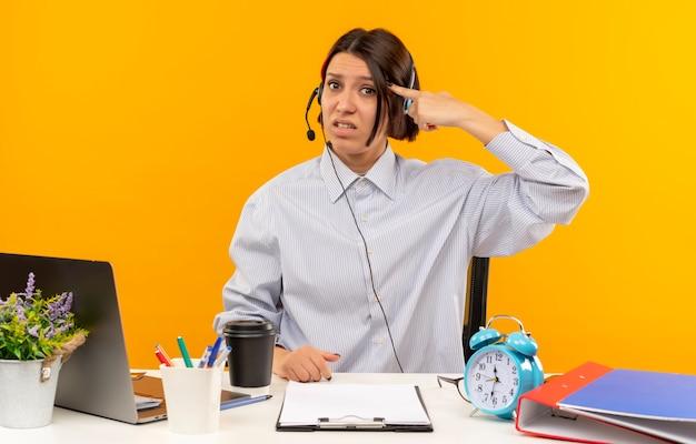 Unzufriedenes junges callcenter-mädchen, das headset trägt, das am schreibtisch mit arbeitswerkzeugen sitzt, die finger auf tempel lokalisiert auf orange hintergrund setzen