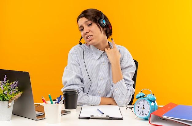 Unzufriedenes junges callcenter-mädchen, das headset trägt, sitzt am schreibtisch mit arbeitstools, die finger erhöhen, lokalisiert lokalisiert auf orangefarbenem hintergrund