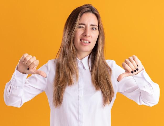 Unzufriedenes junges hübsches kaukasisches mädchen daumen nach unten mit zwei händen auf orange