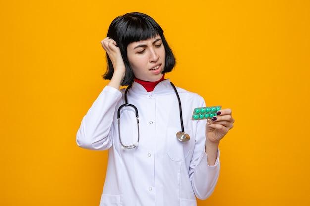 Unzufriedenes junges hübsches kaukasisches mädchen in arztuniform mit stethoskop, das die hand auf den kopf legt und die tablettenverpackung hält