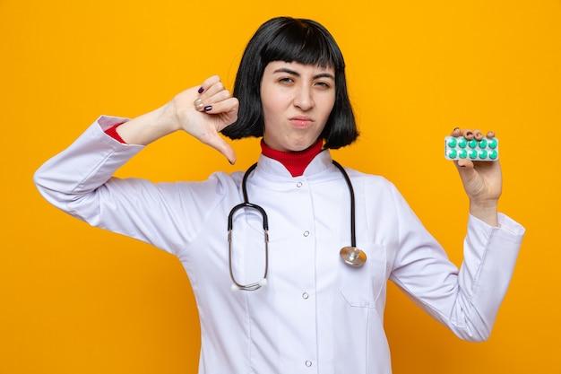 Unzufriedenes junges hübsches kaukasisches mädchen in arztuniform mit stethoskop, das pillenverpackung hält und herunterdrückt