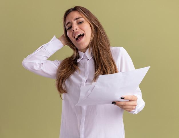 Unzufriedenes junges hübsches kaukasisches mädchen legt die hand auf den kopf und betrachtet leere papierblätter einzeln auf olivgrüner wand mit kopierraum