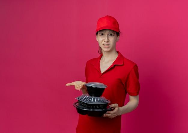 Unzufriedenes junges hübsches liefermädchen, das rote uniform und mütze hält und mit der hand auf lebensmittelbehälter zeigt, die auf purpurrotem hintergrund mit kopienraum lokalisiert werden
